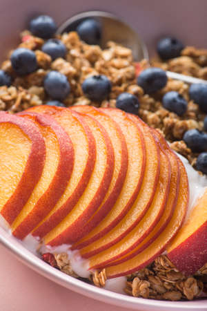 Bowl of granola with yogurt, peach slices and bluberry on a pastel pink background. Morning food dessert. Healthy breakfast snack.