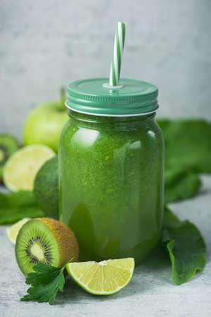 Frullato di disintossicazione verde in barattolo di vetro da spinaci, kiwi, lime, avocado su uno sfondo di pietra chiara. Dieta e vitamina frutta sana bevanda, concetto di cibo vegetariano.