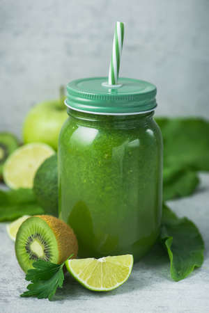 Green detox smoothie in glass jar from spinach, kiwi, lime, avocado on a light stone background. Diet and vitamin fruit healthy drink, vegetarian food concept.