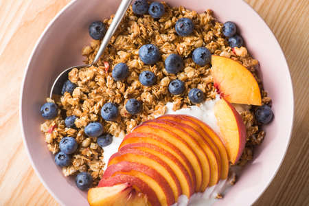 Bowl of granola with yogurt, peach slices and bluberry on a wooden table. Morning food dessert. Healthy breakfast. top view