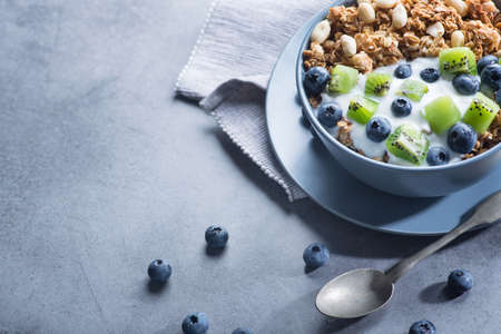 Healthy breakfast with granola cereal with blueberry, kiwi, yogurt and peanuts in blue bowl on a stone. Morning sweet dessert snack. copy space