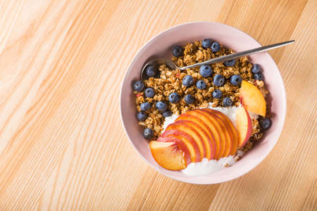 Bowl of granola with yogurt, peach slices and bluberry on a wooden table. Morning food dessert. Healthy breakfast. top view. copy space 写真素材