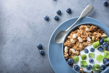 Healthy breakfast with granola cereal with blueberry, kiwi, yogurt and peanuts in blue bowl on a stone. Morning sweet dessert snack.  top view. copy space 写真素材