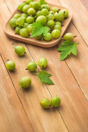Fresh and natural gooseberry with mint on a wooden table. Berry organic, vitamin food.