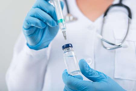 진료실에서 독감 백신을 손에 들고 있는 여성 의사. 병원에서 백신 접종. 스톡 콘텐츠