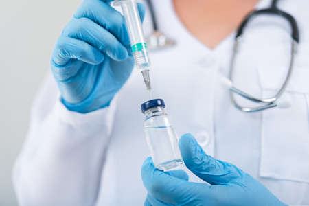 Doctora sosteniendo la vacuna contra la gripe en las manos en la sala de la clínica. dosis de vacunación en el hospital. Foto de archivo