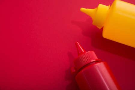 Contenitori in plastica con ketchup e senape su sfondo rosso. concetto di fast food. Archivio Fotografico