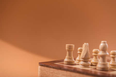 Wooden chess pieces on a brown background.