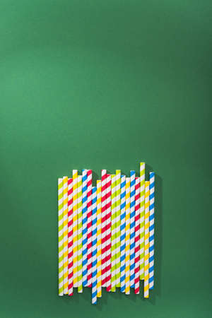 Bright colored cocktail straw on a color green background. recycling eco concept. minimal style. flat lay. top