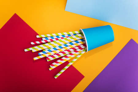 Bright colored cocktail straw in paper cup on a color background. recycling eco concept. pop art style. flat lay. top