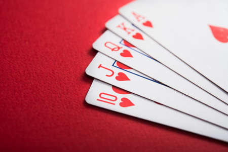 Hearts royal flash cards on a red table. Poker casino game.