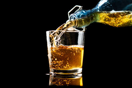 Pouring fresh gold apple cider in a glass on a black background