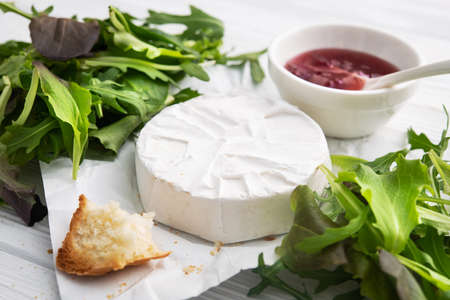 Milk brie cheese with cranberry jam on a white background