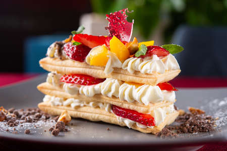 Tasty fresh italian mille-feuille dessert with strawberry on a restaurant table. sweet high-calorie food background.
