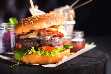 Big burger with beef cutlet, bacon and egg on a black background. american fastfood.