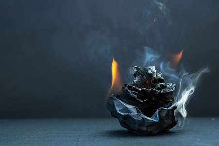 Crumpled paper ball burns with fire on a black background. Bad idea. Failure.
