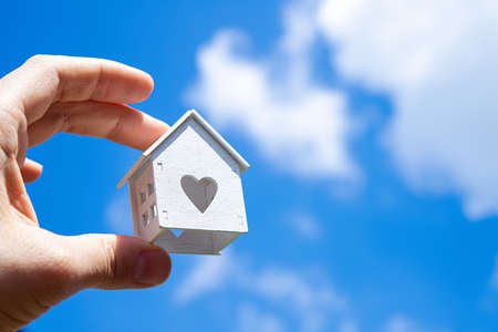 Man holding small white model of house against sky background. Concept of buy new home. Love heart window. Stockfoto
