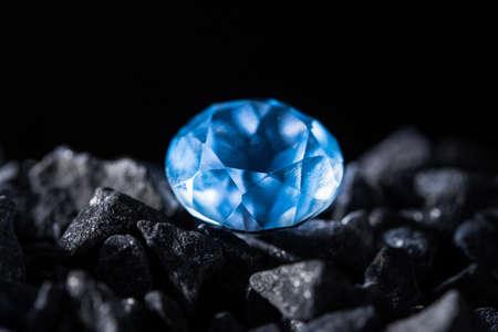 One blue big diamond among stones black background.