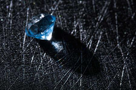 Closeup photo of blue natural diamond stone on black background. jeweler work, stone insertion.