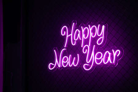 Abstract purple colored lifht bright neon text Happy New Year on a black cage mesh background.