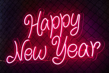 Abstract colored lifht bright neon text Happy New Year on a black cage mesh background. Stockfoto