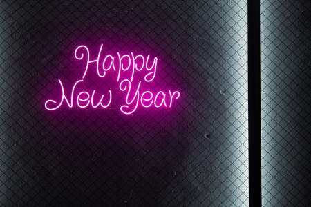 Abstract pink colored lifht bright neon text Happy New Year on a black cage mesh background.