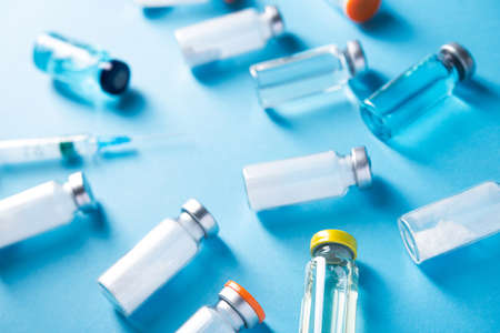 Bottles with vaccine coronavirus on a blue table background. Flat lay covid 19. Top view.