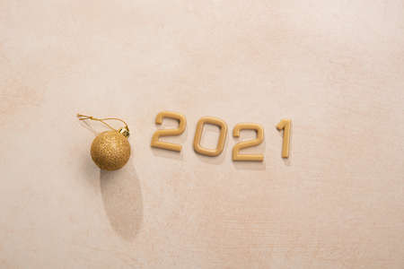 Golden 2021 number with happy new year on stone background. Top view.