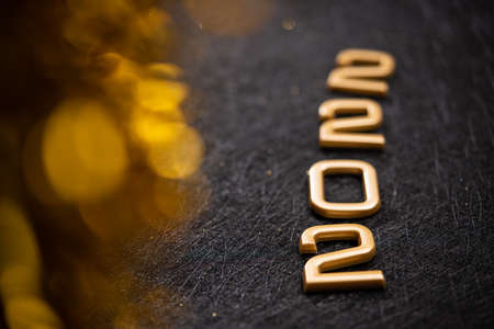Golden 2022 number on a black background. Happy New Year celebrate banner.