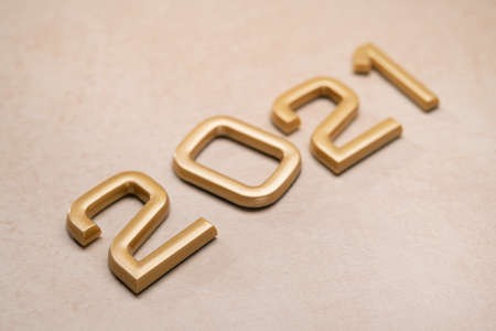 Golden 2021 number with happy new year on stone background.