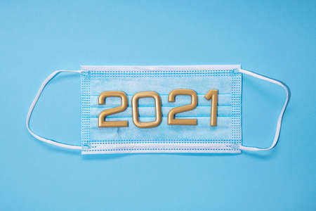 Medical mask against coronavirus. Vaccination begins in 2021. The numbers are golden. Blue background. Stockfoto