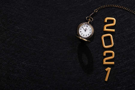 Happy New Year 2021 golden numbers with retro stopwatch five minutes before. Top view.