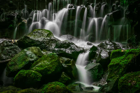Mini waterfall and mossy river rocks in a cloudy weather