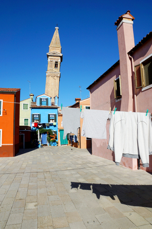 drying clothes on a background of multi-colored facades of the island of Burano, Venice, Italy