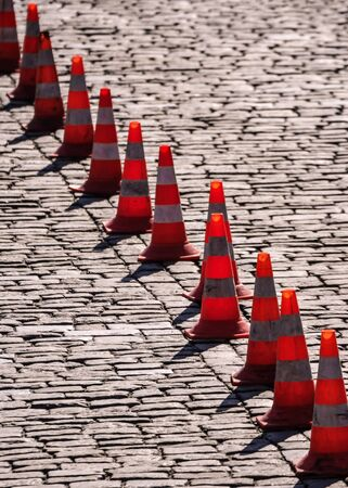 road safety cones on a cobblestone street photo