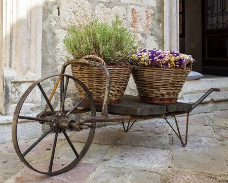 oude kruiwagen met manden van bloemen Stockfoto