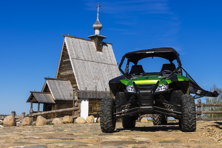 museum rally: RLES, RUSSIA - MAY 9: the Arctic Cat Wildcat ATV - against old wooden church in the city the Ples on May 9, 2015. a series of motor-all-terrain vehicles with classical configuration of the buggy