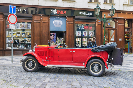PRAGUE, CZECH REPUBLIC MAY-19: Red old car waiting for tourists on the street in Prague on May 19, 2016. These cars are usually rented by tourists visiting Prague. Editorial