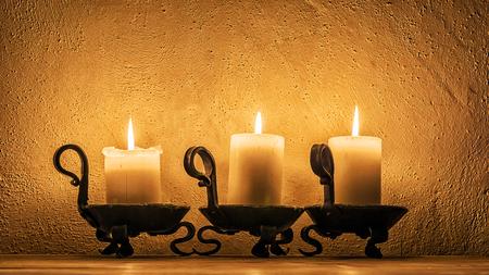 Drie kaarsen branden in het donker Stockfoto