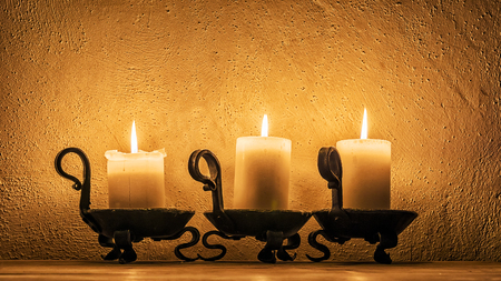 Three candles burning in the dark