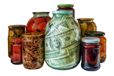 bank with dollars on a background of glass jars with canning vegetables and jam. Concept: blank for the future