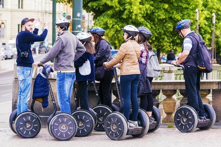 guia de turismo: REPÚBLICA CHECA, PRAGA - 21 de mayo, 2016: un guía dirige a un grupo de turistas que viajan en el Segway por las calles de Praga