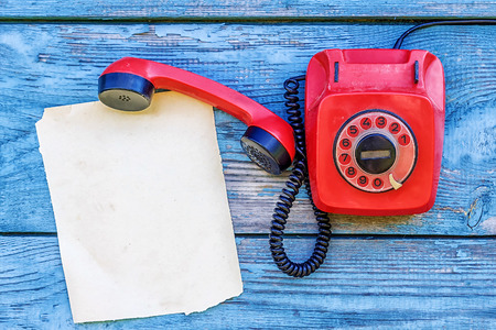 phone cord: Red retro telephone and a sheet of paper for records