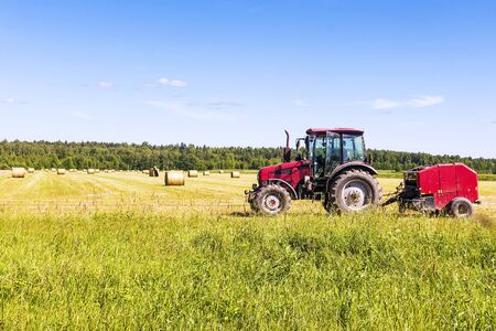 Red tractor in the field on a hay