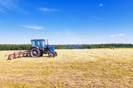 Old tractor in a field in the hay Stock Photo