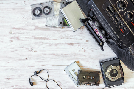 earpiece: cassette player, cassette recorder and audio tape on a wooden background