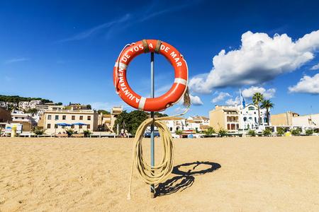 lifebuoy on the beach in Tossa de Mar, Spain. an inscription on a circle in Catalan: Tossa de Mar