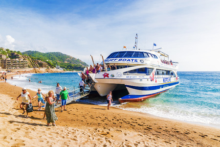 TOSSA DE MAR,SPAIN - SEPTEMBER 16, 2015: Passengers disembark from a boat on the beach in Tossa de Mar on the Costa Brava Editorial