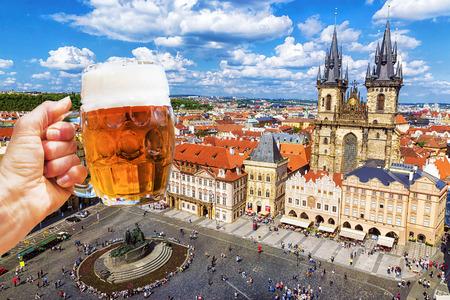 Hand met een mok bier op de achtergrond van het oude stadsplein in Praag