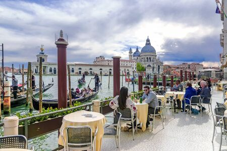 ITALY, VENICE APRIL 19, 2017: A street cafe on a grand canal in the background of the Church of Santa Maria in Venice Banque d'images - 137507597